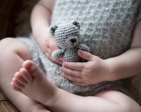 Photograph of a baby's feet and hands holding a crochet teddy bear by Christchurch baby and family photographer Kirsten Naomi Photography