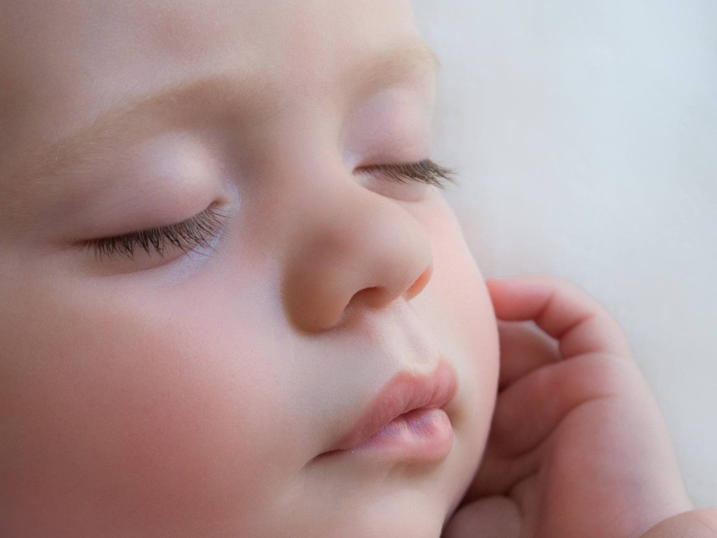 Close-up portrait photograph of a sleeping baby boy with gorgeous eyelashes and lips