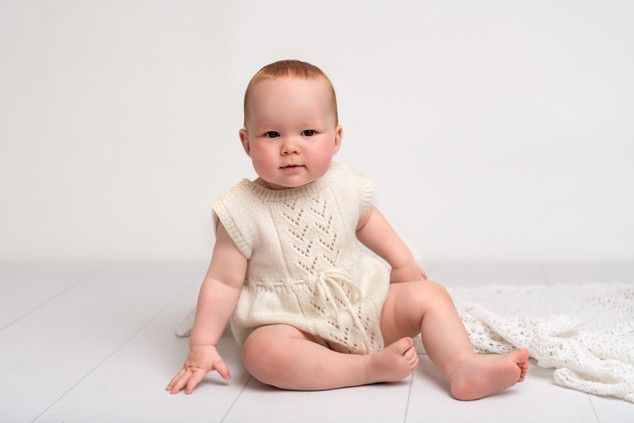 Portrait of a red headed baby boy in a vintage cream knit by Christchurch Baby and Family Photographer Kirsten Naomi Photography