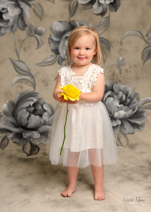 Portrait of a small girl in a white ruffled dress by Christchurch family photographer Kirsten Naomi Photography
