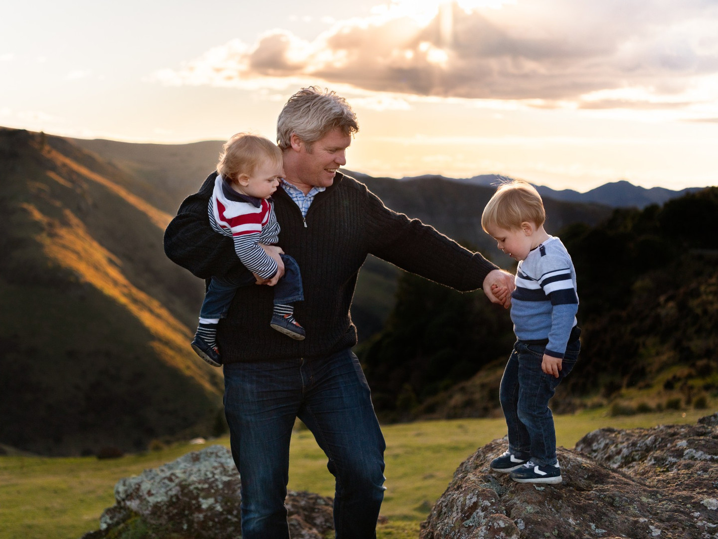 Portrait photograph of a dad and his two son on a hill at sunset during a family photography session