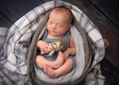 Photograph of a newborn baby boy holding a cute tiny lion by Christchurch newborn baby & family photographer Kirsten Naomi Photography