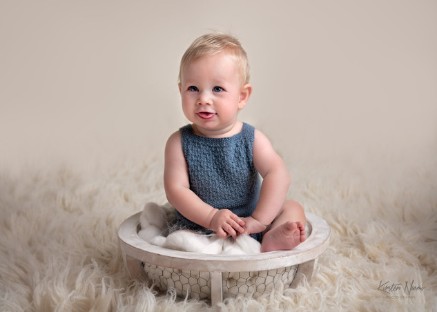 Portrait of smiling Baby boy in a blue knit romper by Christchurch Baby and Family Photographer Kirsten Naomi Photography