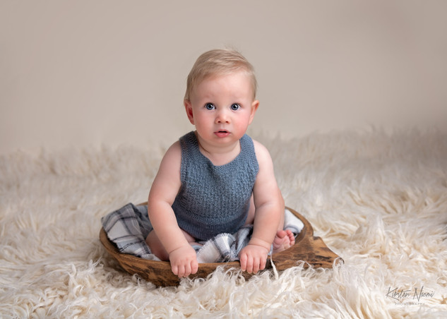 Portrait of Baby boy in a blue knit romper by Christchurch Baby and Family Photographer Kirsten Naomi Photography