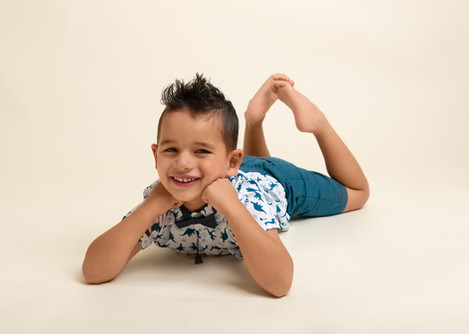 Portrait of a four year old boy lying on his tummy by Christchurch family photographer Kirsten Naomi Photography