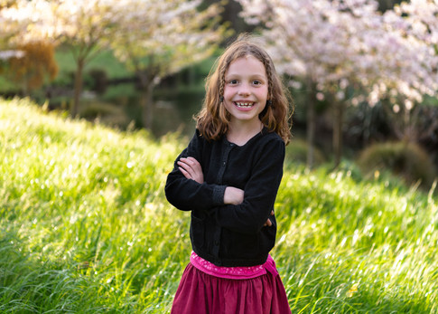 Photograph of a girl with a stunning smile in front of a blossom tree by Christchurch family photographer Kirsten Naomi Photography | Family Portraits | Lifestyle Photography | Environmental Portraits | Simply Authentic