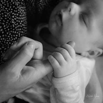 Black and white portrait of a newborn baby boy holding his mother's finger during a photography session at home with Christchurch newborn and baby photographer Kirsten Naomi Photography