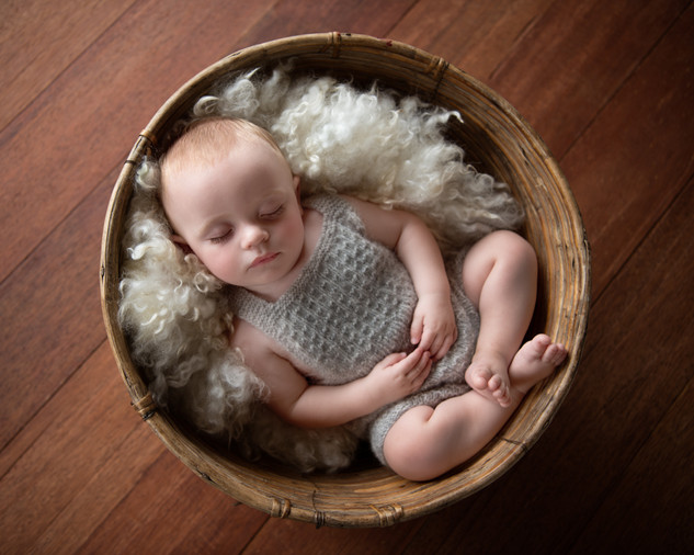Photograph of a sleeping baby boy in a basket by Christchurch baby and family photographer Kirsten Naomi Photography