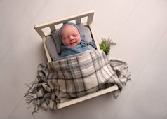 Photograph of a smiling newborn baby boy in a tiny bed by Christchurch newborn baby & family photographer Kirsten Naomi Photography