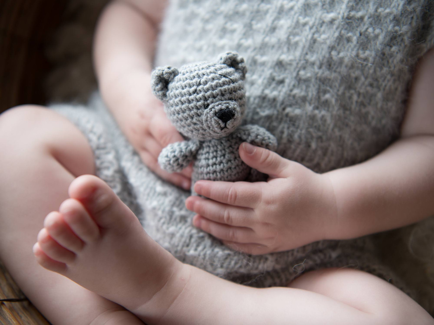 Close-up portrait photograph of a baby's hands and feet, holding a crochet teddy bear