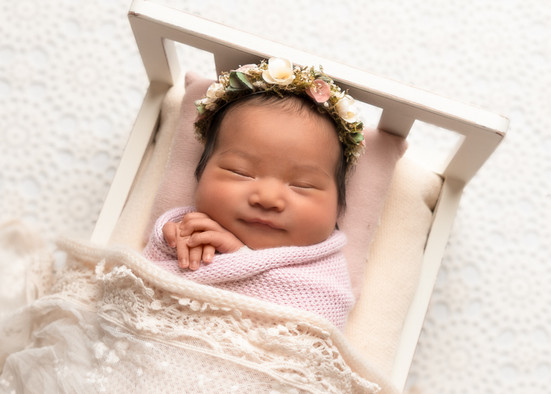 Portrait of a beautiful baby girl in a tiny bed by Christchurch newborn baby & family photographer Kirsten Naomi Photography