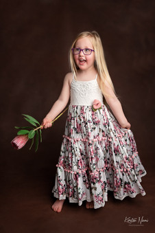 Portrait of a small girl in a white and floral dress by Christchurch family photographer Kirsten Naomi Photography