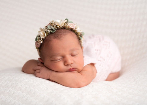 Portrait of a beautiful baby girl wearing a floral crown with her head on hear hands by Christchurch newborn baby & family photographer Kirsten Naomi Photography