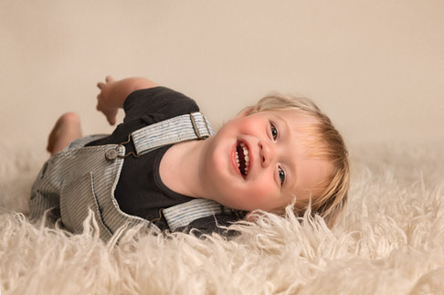 Portrait of a toddler rolling and laughing by Christchurch child and family photographer Kirsten Naomi Photography