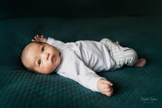 Portrait of a newborn baby boy on a dark green quilt during a photography session at home with Christchurch newborn and baby photographer Kirsten Naomi Photography