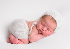 Photograph of a newborn baby girl in a white bonnet by Christchurch newborn baby & family photographer Kirsten Naomi Photography