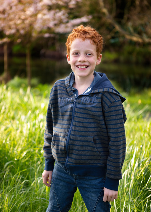 Photograph of a boy with stunning red hair in front of a blossom tree by Christchurch family photographer Kirsten Naomi Photography | Family Portraits | Lifestyle Photography | Environmental Portraits | Simply Authentic