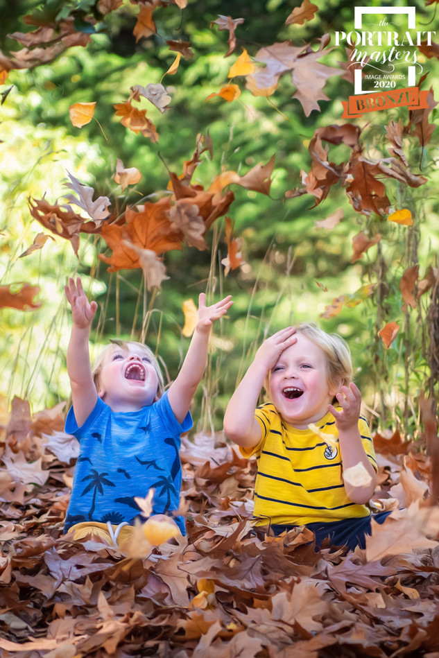 Award winning portrait of two brothers playing in autumn leaves by Christchurch Children and Family Photographer Kirsten Naomi Photography