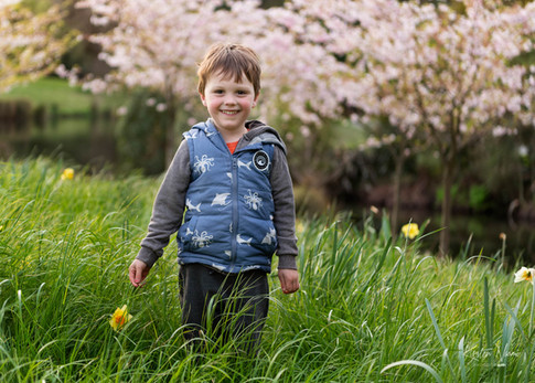 Photograph of a small boy with a flower in front of a blossom tree by Christchurch family photographer Kirsten Naomi Photography | Family Portraits | Lifestyle Photography | Environmental Portraits | Simply Authentic
