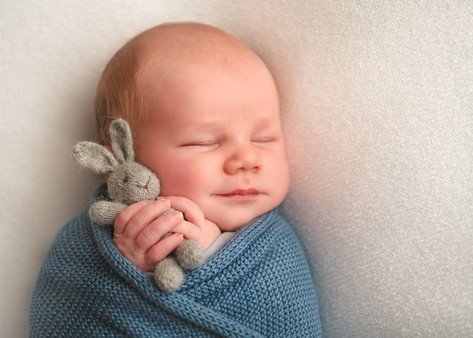 Photograph of a newborn baby boy in a blue wrap with a bunny by Christchurch newborn baby & family photographer Kirsten Naomi Photography