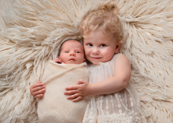 Portrait of a beautiful baby girl being cuddled by her sister by Christchurch newborn baby & family photographer Kirsten Naomi Photography
