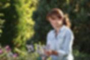 Mature woman gardening in her backyard.j