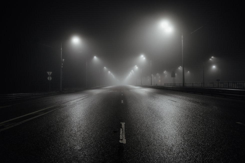 Foggy misty night road illuminated by st