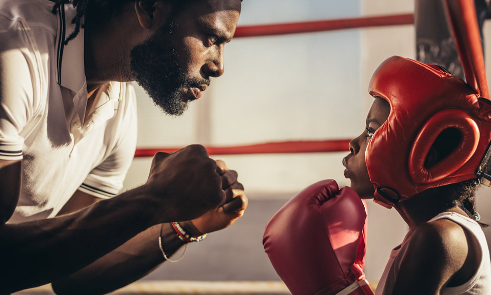 Boxing coach and kid training inside a b