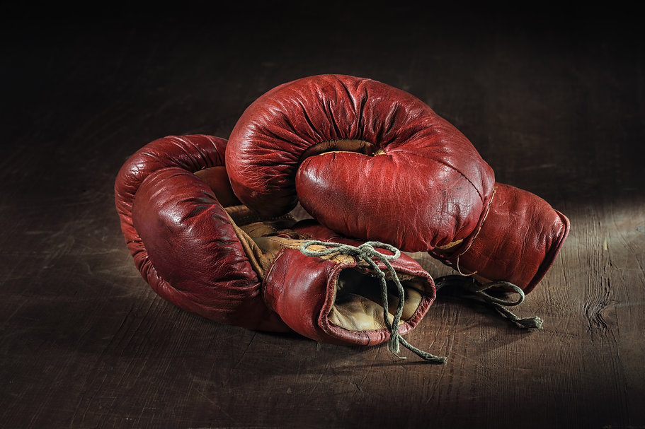 Old red boxing gloves on wooden backgrou
