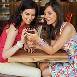 Two girls in a coffee shop, smiling, gos
