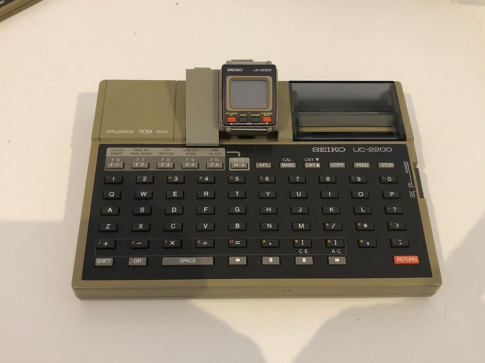 Uma Seiko UC-2000 em sua estação de ancoragem UC-2200, observe a impressora térmica da direita e o pacote ROM à esquerda