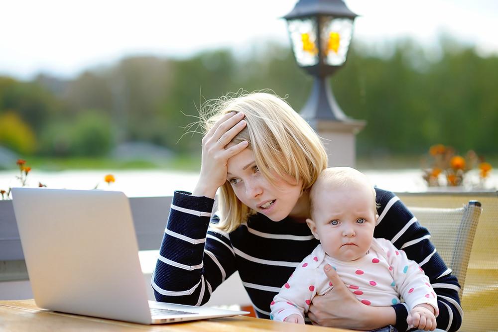 Una madre se muestra preocupada mirando un ordenador mientras su hija observa preocupada al fotógrafo.