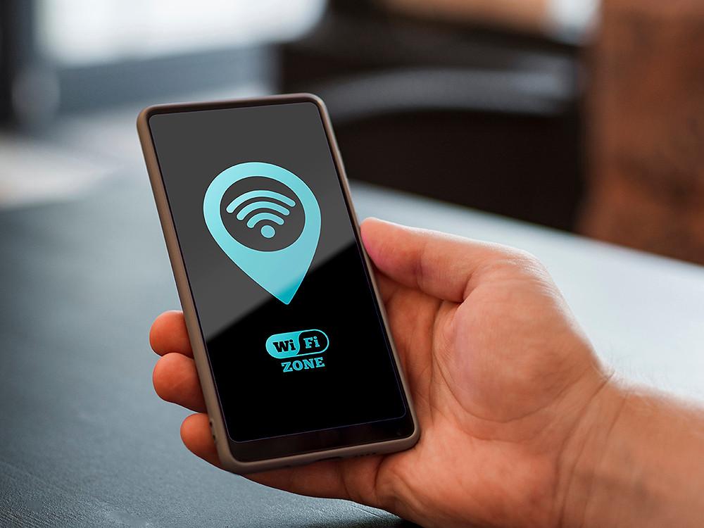 Una mano sujetando un Smartphone en el que se ve un icono Wi-Fi y otro icono con el texto Wifi Zone o Zona Wi-Fi