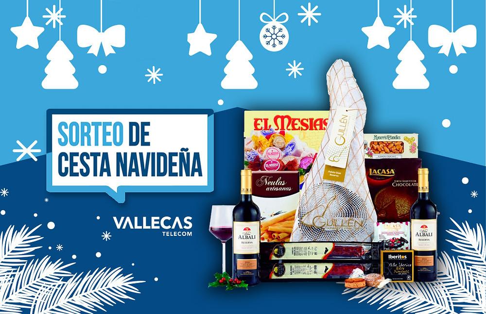 La cesta de Navidad que sortea Vallecas Telecom a sus clientes del Ensanche de Vallecas contiiene una paletilla de Ibérico, Salchichón, polvorones, barquillos, vino de Valdepeñas. Participa.