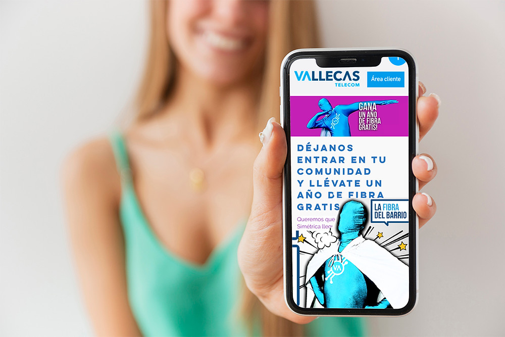 Mujer mostrando pantalla de móvil ocn la web de Vallecas Telecom