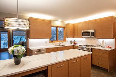 Teak slab mid century modern kitchen with quartz counters.