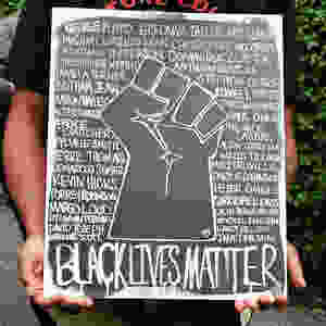 """person holding a black and white sign that shows an illustrated fist in black with names of victims killed by police written in white around it and """"BLACK LIVES MATTER"""" at the bottom"""