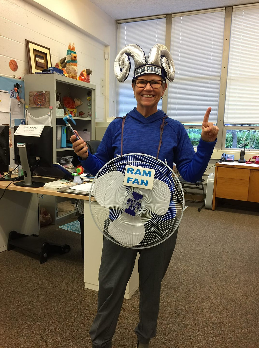 "Traci Huffer dressed as a ""Ram Fan"" for Halloween, wearing a ram horns hat and a fan around her neck."