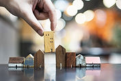 Hand choosing mini wood house model from