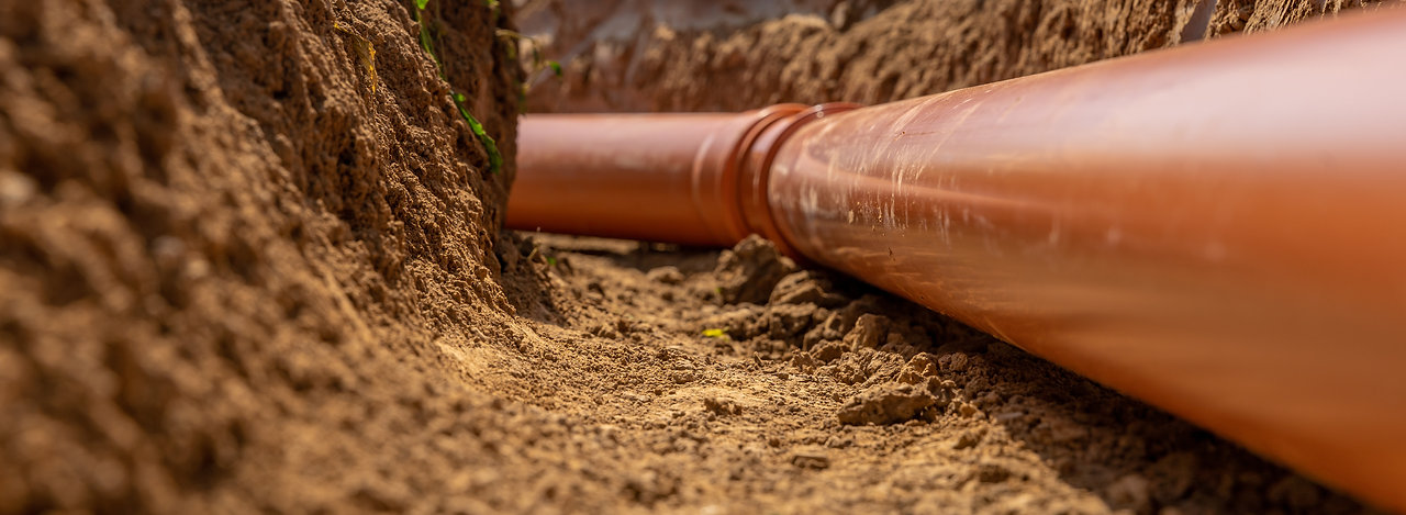 Plastic pipes in the ground during the construction of a building, bunner with copy space.