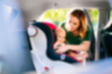 young-mother-putting-baby-boy-in-the-car