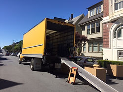 Yellow moving truck with loading ramp