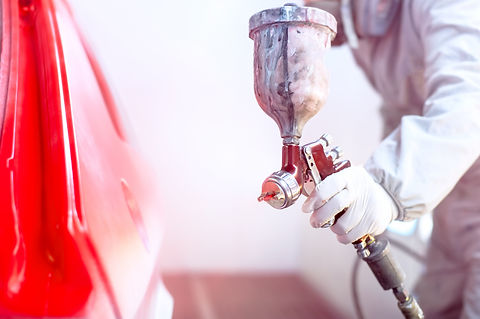 Close-up of spray gun with red paint pai