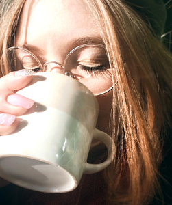 Klara Regina drinking a cup of coffee with the sunlight on her face with her eyes closed.