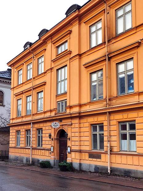 Hälsans hus i Stockholm en regnig dag med orange fasad