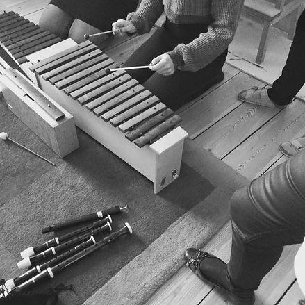 En kvinna spelar marimba sittandes på golvet under en workshop tillsammans med andra deltagare i musikterapi