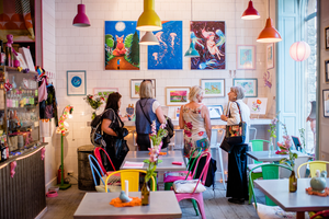 Photograph of Klara Regina's exhibition at the colorful coffeeshop Eat with Jonna. Three women look at the artworks.