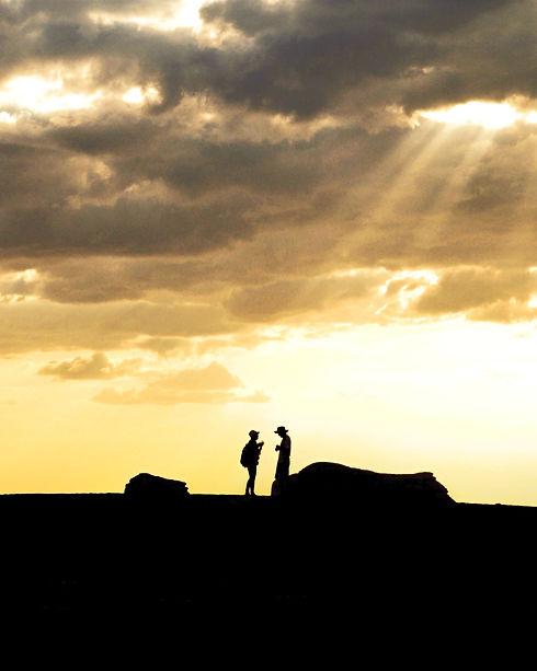 kärlekspar i samtal, siluetter mot gul himmel