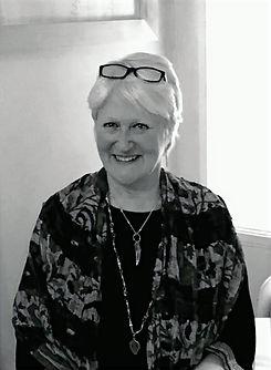 Svartvitt foto på Anita Båge, Dipl. Uttryckande konstterapeut, psykodramaledare och filmproducent, iklädd i sjal, smycken och glasögon