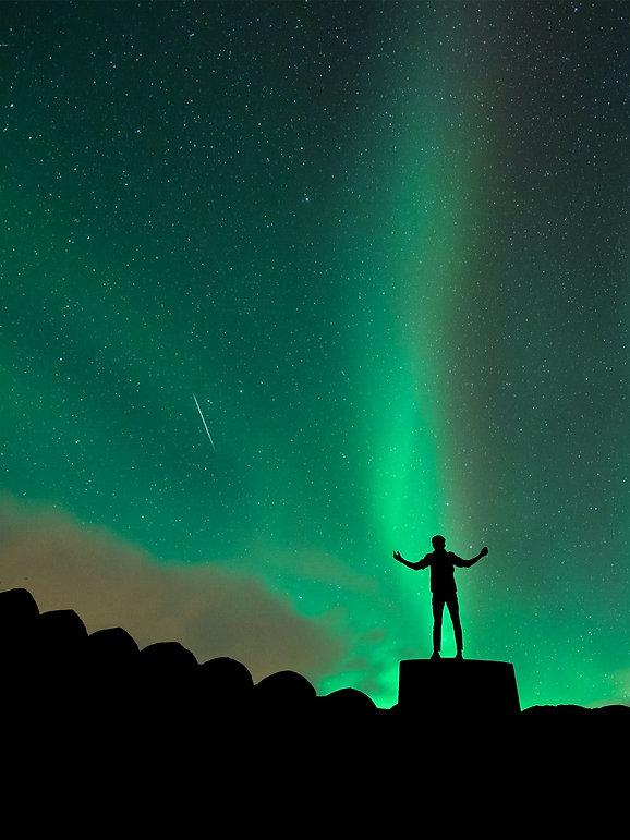 siluett med armarna utsträckta i norrsken